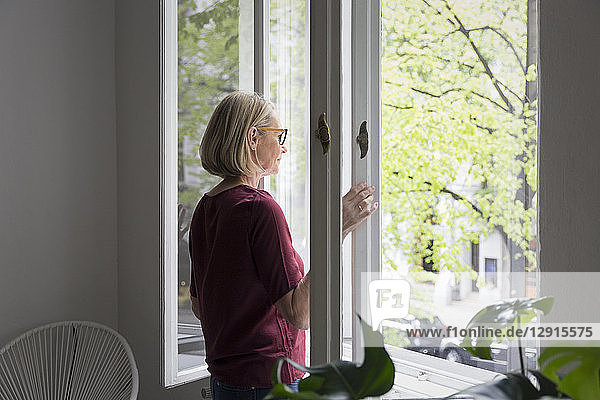 Mature woman at home opening the window