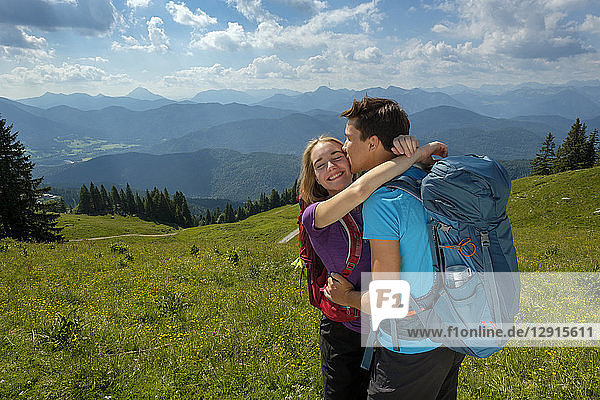 Germany  Bavaria  Brauneck near Lenggries  happy young couple hugging and kissing in alpine landscape