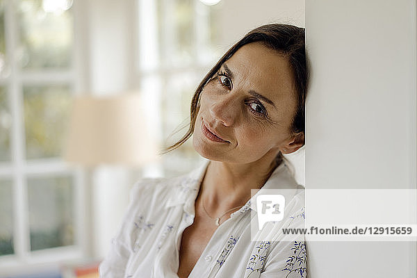 Portrait of mature woman leaning against doorframe