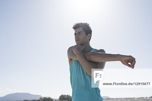 Spain  Canary Islands  Fuerteventura  young man stretching his arm under blue sky