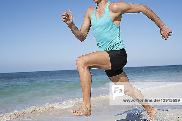 Spain  Canary Islands  Fuerteventura  young man exercising on the beach