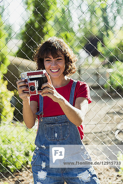 Portrait of smiling woman with instant camera