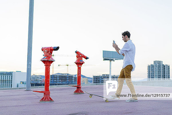 Young man with a skateboard using cell phone
