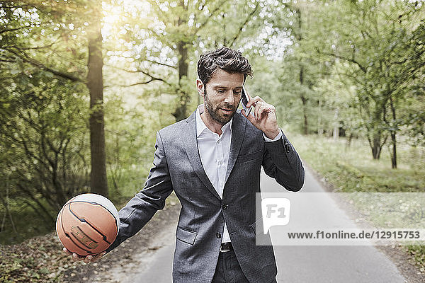 Businessman with basketball talking on smartphone on rural road