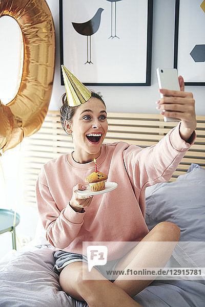 Woman blowing out the candle on the birthday cake and making a selfie