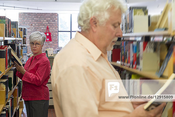 Senior woman watching man reading book in a city library