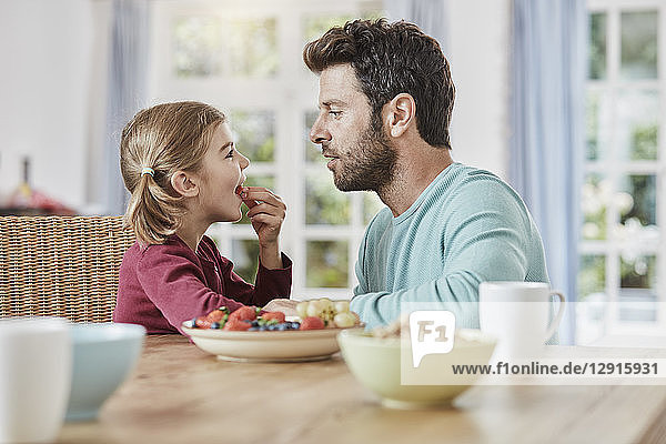 Father and daughter eating fruit at home