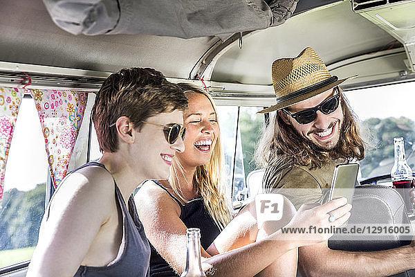 Happy friends inside van looking at smartphone