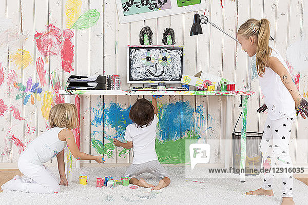 Three girls painting office with finger paint