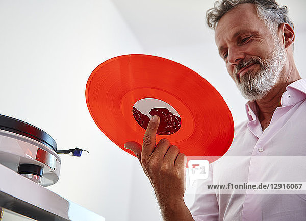 Smiling mature man holding red vinyl record