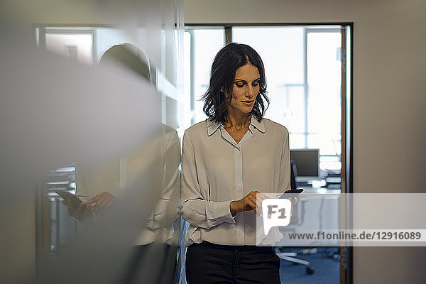 Businesswoman in office reading messages on her smartphone