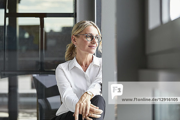 Serene businesswoman sitting on ground  looking out of window