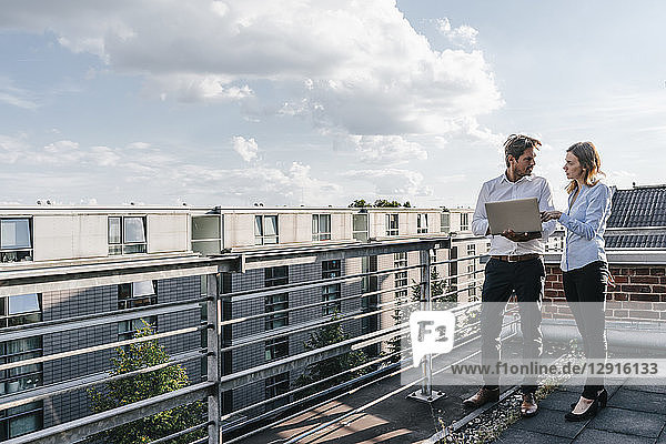Business people standing on balcony  discussing  using laptop