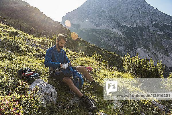 Austria  Tyrol  Hiker taking a break  sitting on a rock  searching his rucksack