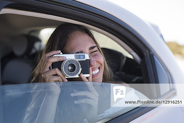 Woman sitting in car  taking pictures with a camera