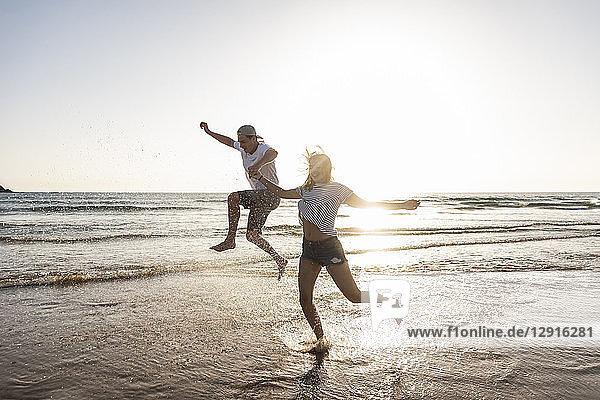 Young couple having fun at the beach  splashing water in the sea