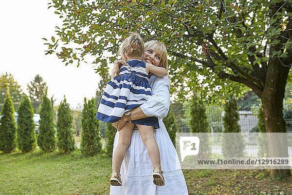 Happy mother carrying her daughter in garden