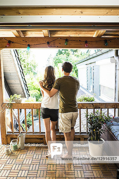 Rear view of couple standing on balcony