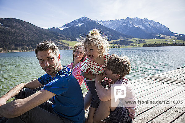 Austria  Tyrol  Walchsee  happy family sitting on a jetty at the lakeside