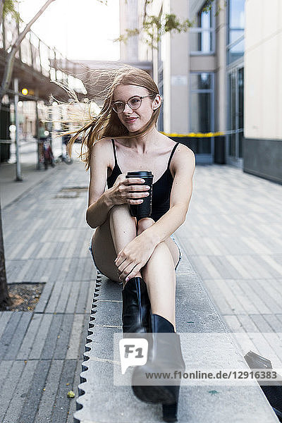 Young woman sitting on a wall  drinking coffee to go