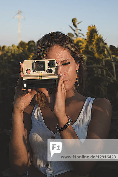 Young woman in a field of sunflowers taking pictures with an instant camera