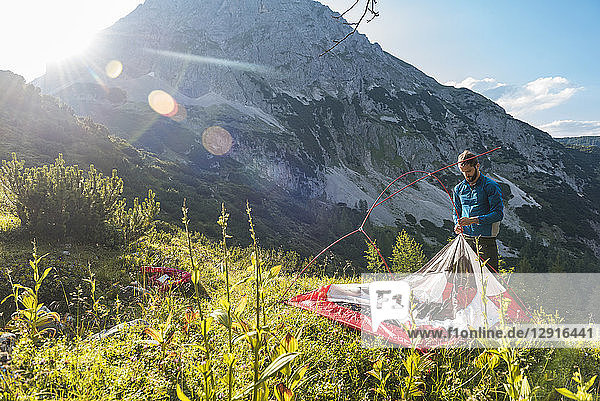 Austria  Tyrol  Hiker setting up his tent in the mountains