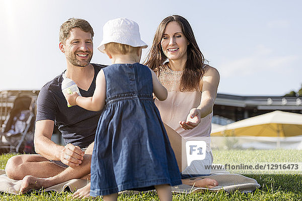 Happy family with little daughter on a meadow