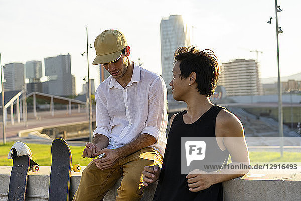 Two young men resting next to skateboards at a wall