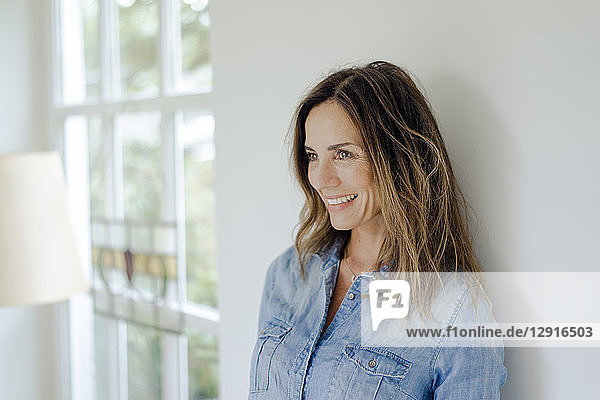 Portrait of smiling mature woman at home leaning against a wall