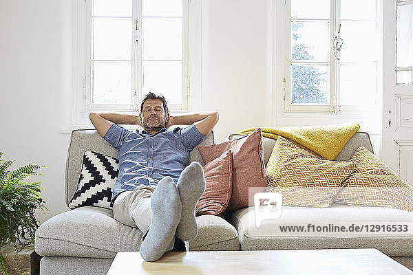 Man sitting on couch at home  relaxing