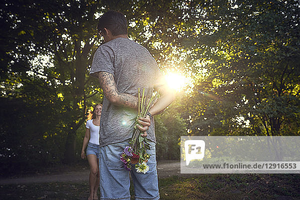 Young man meeting his girlfriend in a park  gifting her with flowers