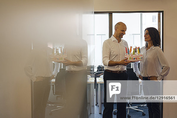 Businessman gifting his colleague with a birthday cake in office