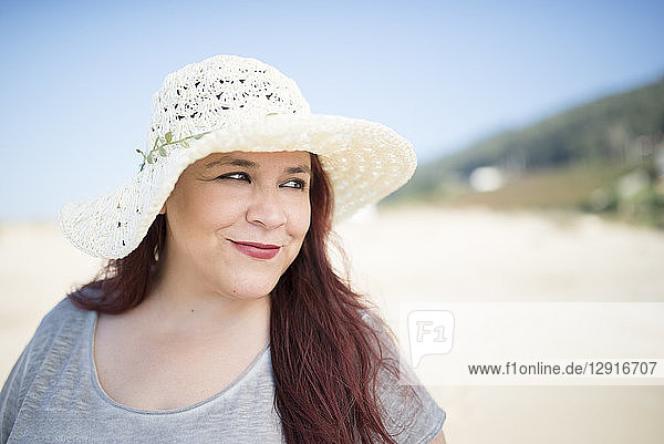 Portrait of smiling woman wearing summer hat on the beach