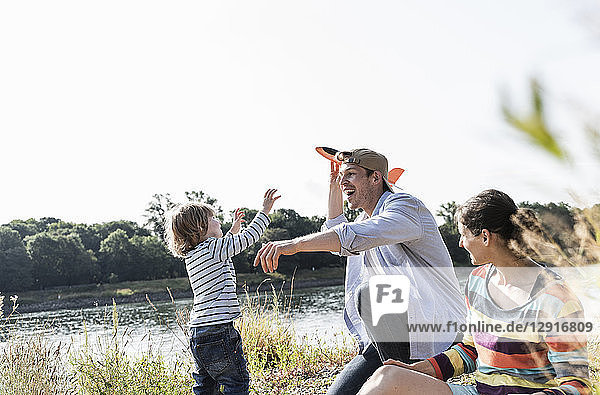Happy family relaxing at the riverside  father and son playing with toy plane