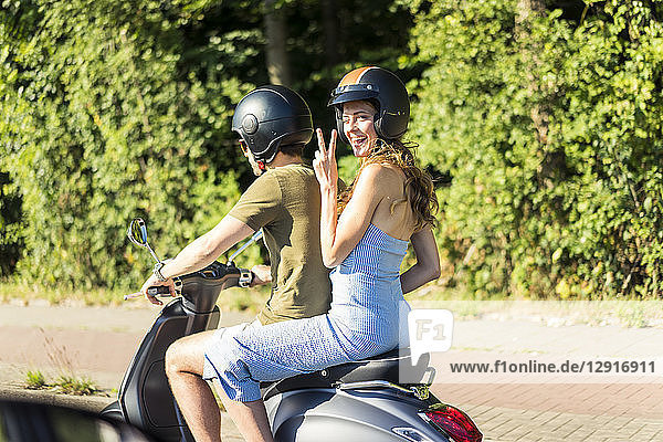 Happy couple riding motor scooter in summer