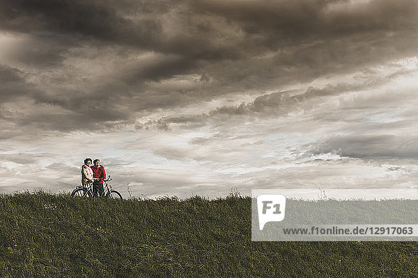 Senior couple with bicycles in rural landscape under cloudy sky