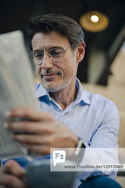 Businessman sitting in coffee shop  reading newspaper  drinking coffee