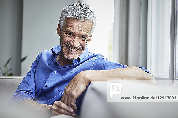 Portrait of smiling mature man sitting on couch at home
