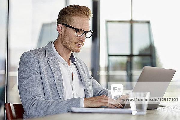 Businessman using laptop on desk in office