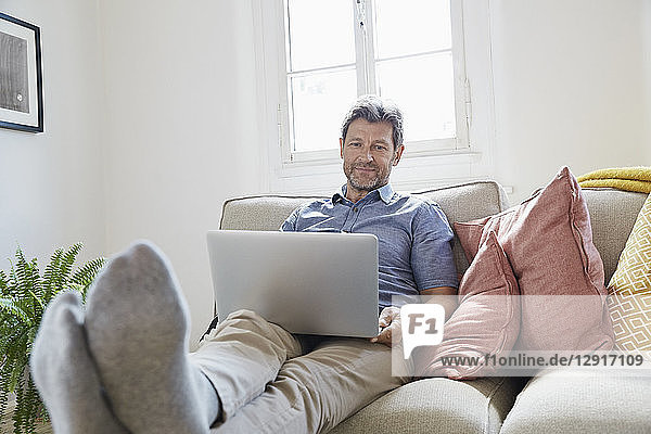 Man sitting on couch at home  using laptop