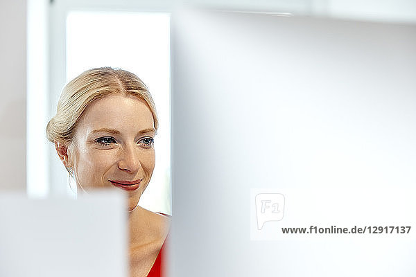 Portrait of smiling young woman working on computer