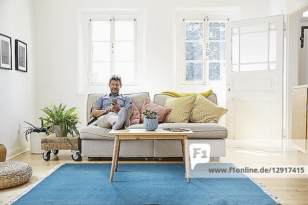 Man sitting on couch at home  using smartphone