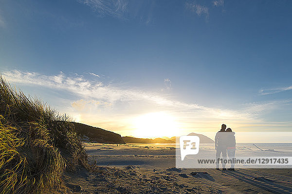 New Zealand  South Island  Puponga  Wharariki Beach  Couple on the beach at sunset