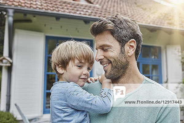 Happy father carrying son in front of their home