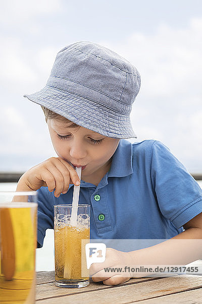 Boy blowing bubbles with staw in his soft drink