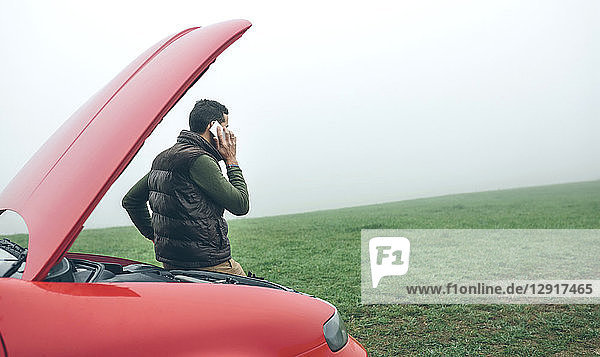 Man talking on cell phone next to broken car