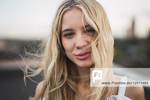 Portrait of smiling blond young woman outdoors