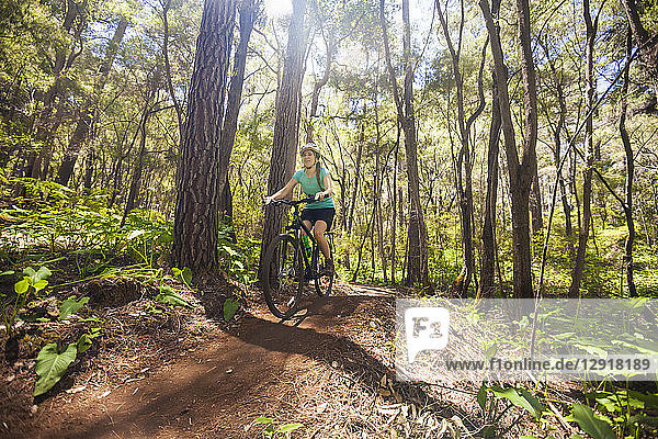 Front view of young woman mountain biking in forest on The Pines Trails  Margaret River  Western Australia  Australia