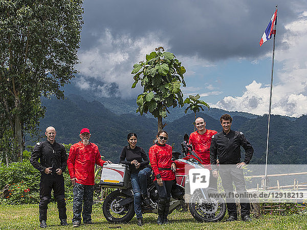 Group of friends posing together beside motorcycle with forested hill in background  Nan ¬ÝMueang¬ÝChiang¬ÝRai¬ÝDistrict  Thailand