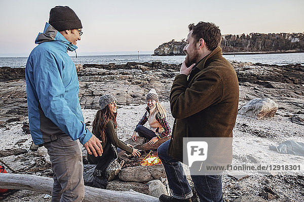 Four adult friends talking and smiling around campfire while camping on rocky coastal beach in autumn  Portland  Maine  USA